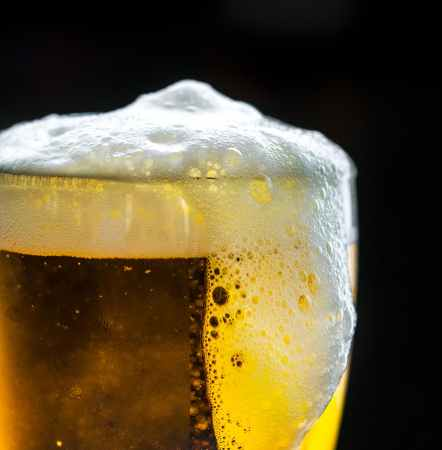 photo of glass overflowing with beer